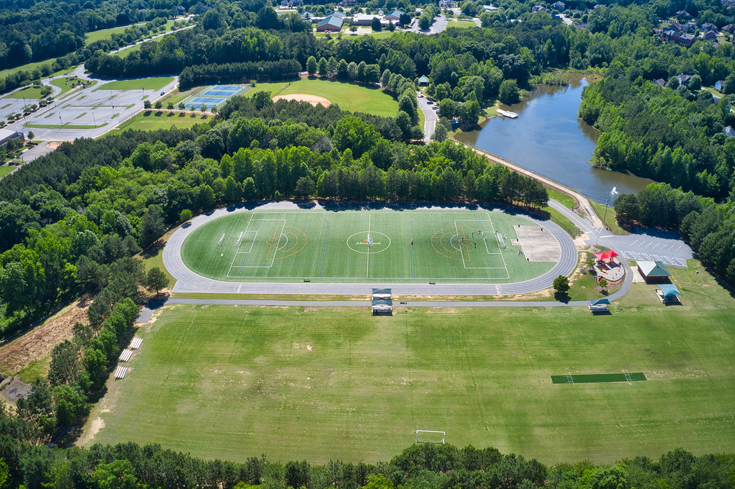 Panoramic above view of recreation center in a suburb park which has soccer field, running track, tennis courts and baseball field