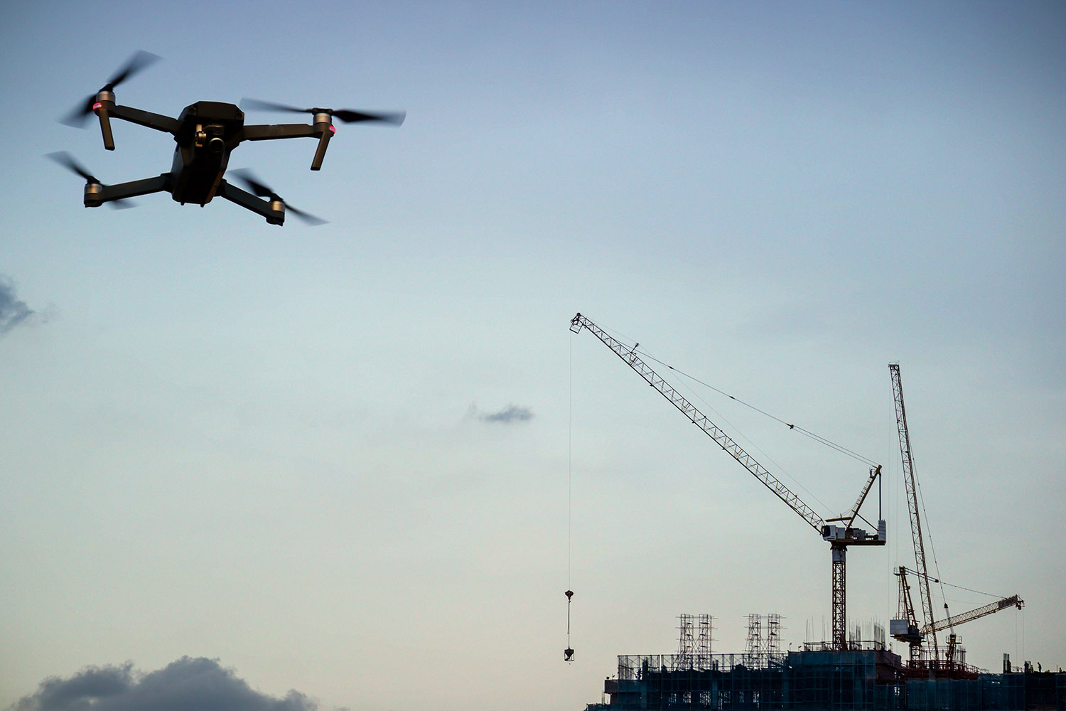Drone with camera flying on Construction site with crane. double exposure